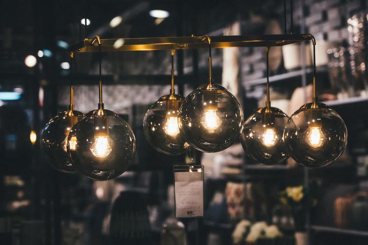 Close-up of illuminated pendant lights hanging in restaurant