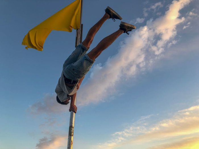 Low Angle View Of Man Balancing On Pole Against Sky During Sunset