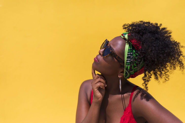 Contemplating young woman wearing sunglasses against yellow background