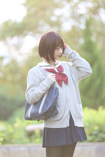 Young woman in school uniform at park