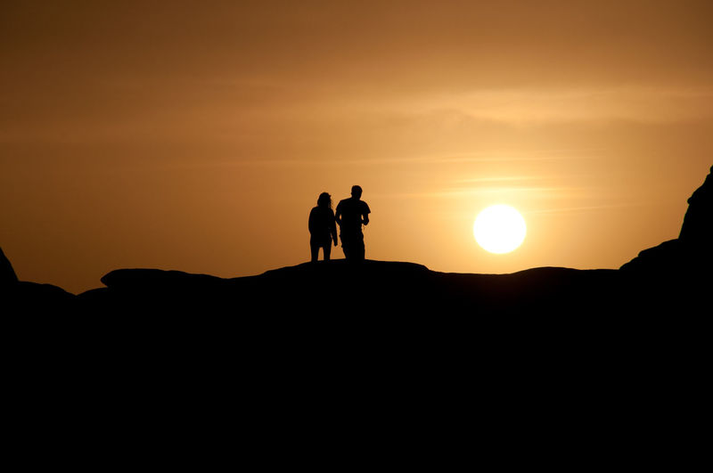 Silhouette of people standing on mountain at sunset