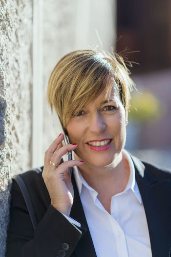 Smiling businesswoman using mobile phone standing outdoors