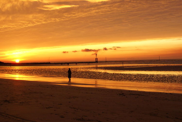 Silhouette Person Standing At Beach Against Sky During Sunset