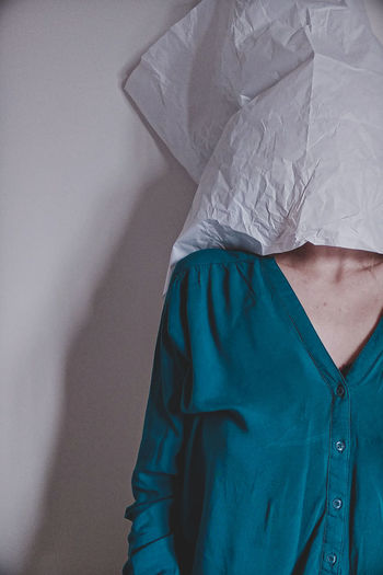 Woman covering face standing by wall at home