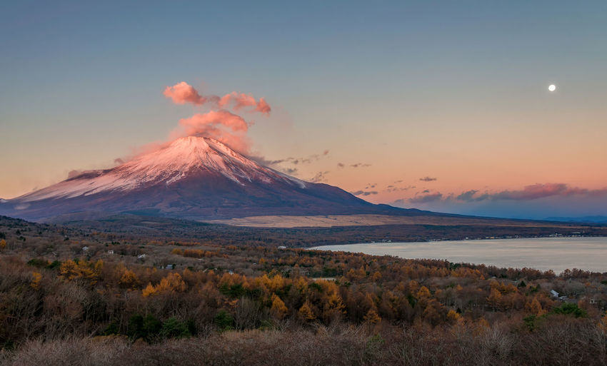 Red Fuji and clouds over mountain in morning sunlight and full Moon in the sky. Japan Yamanaka Lake Beauty In Nature Environment Fuji Idyllic Land Landscape Mountain Mountain Peak Nature No People Non-urban Scene Outdoors Scenics - Nature Sky Snow Snowcapped Mountain Tranquil Scene Tranquility Travel Destinations Volcano