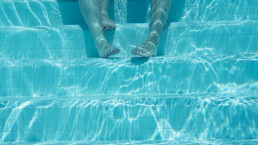 Low section of person swimming in pool