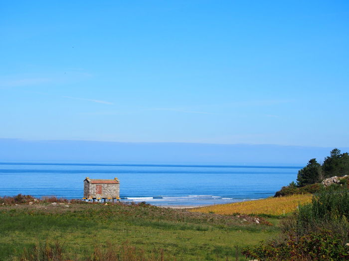 Galicia, Spain Muxía Architecture Beach Beauty In Nature Blue Building Exterior Built Structure Day Grass Horizon Over Water Nature No People Outdoors Scenics Sea Sky Tranquil Scene Travel Destinations Water