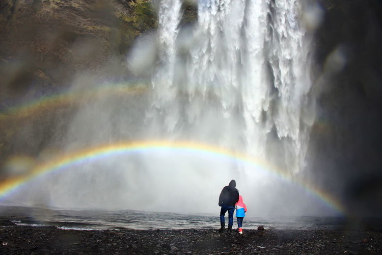 Rear view of man standing against rainbow in water