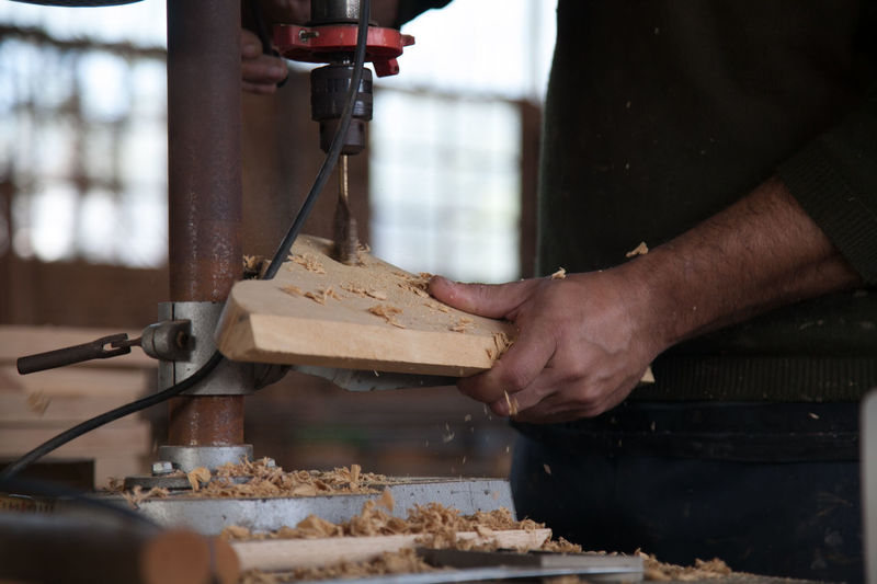 Midsection of carpenter using machinery for cutting plank at workshop