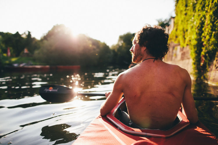 Rear view of shirtless man kayaking on river