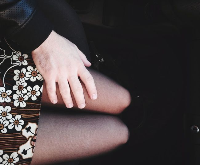 Cropped hand of man touching girlfriend thigh in car