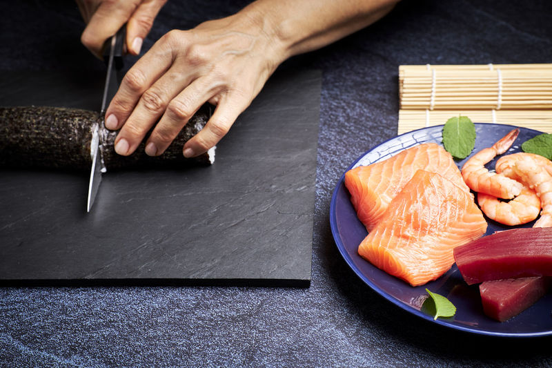 High angle view of man preparing fish on table
