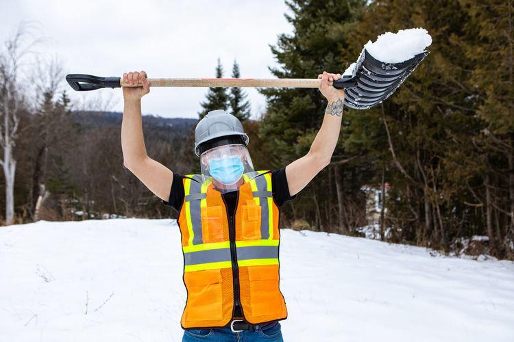 Full length of man holding umbrella in snow