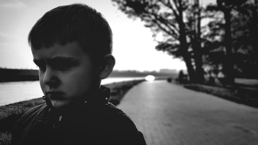 Boy Standing On Street By Lake Against Sky
