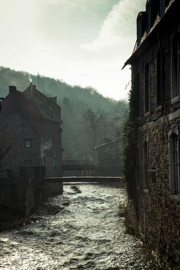 Bridge over canal amidst houses against sky