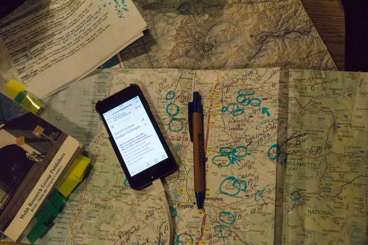 Planning a route to see all the covered bridges in Oregon, USA, on one traveling road trip is a challenge Annotations Book Close-up Covered Bridges Of Oregon Document Education Map No People Open Oregon Paper Pen Planning A Trip Research Smartphone Still Life Tilt Travel Traveling