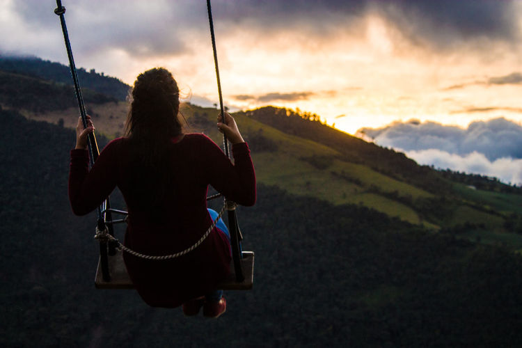 Rear view of woman sitting on swing against sky during sunset