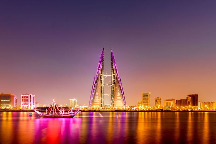 Beautiful view of the Seafront with illuminated World Trade Center and other high rise buildings in the city. Architecture Bahrain Boat Bridge - Man Made Structure Building Exterior City Cityscape Clear Sky Futuristic Illuminated Modern Night No People Outdoors Sky Skyscraper Travel Destinations Urban Skyline World Trade Center WTC