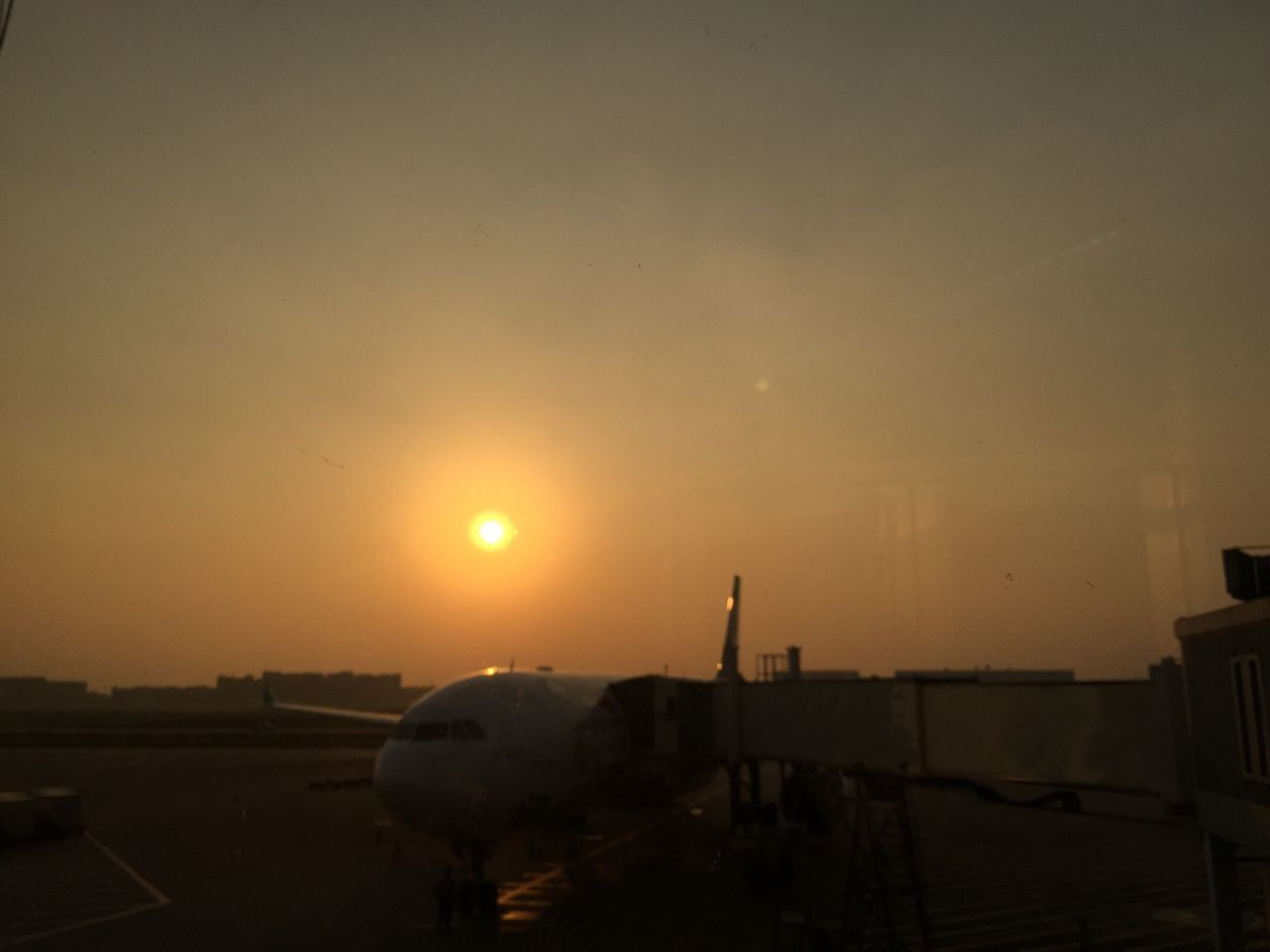 sunset, sun, air vehicle, transportation, sky, silhouette, airplane, mode of transport, outdoors, airport, nature, real people, airport runway, men, one person, commercial airplane, day, people