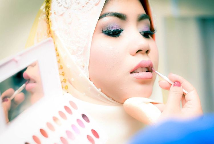 Close-up of young woman applying make-up