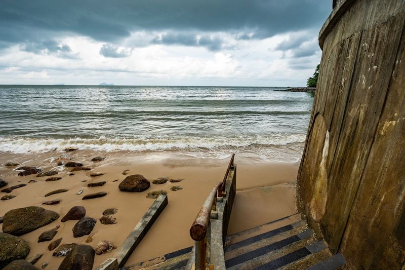 Shipwreck at beach against cloudy sky