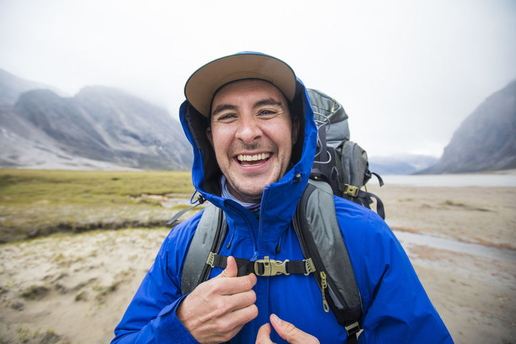 Portrait of happy man wearing hat against mountains