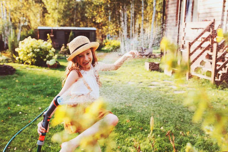 Smiling girl watering plants in garden