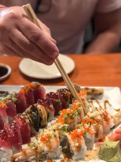 EyeEm Selects Japanese Food Asian Food Sushi Indoors  Rice One Person Seafood Chopsticks Healthy Eating Meal Dinner Close-up Food Human Hand Hand Freshness Food And Drink Indoors  Human Body Part Ready-to-eat Wellbeing Focus On Foreground Holding Plate Dinner