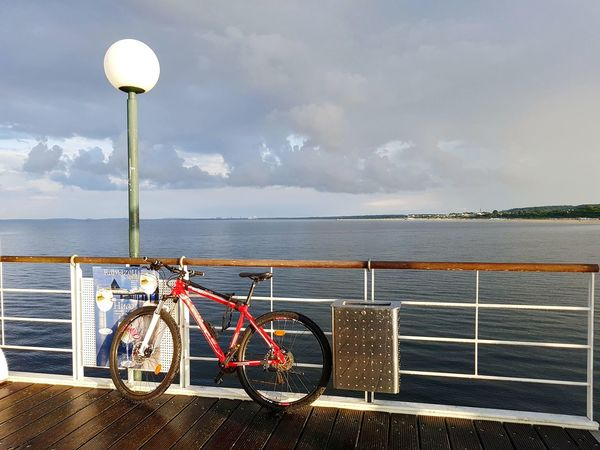 Still Life with bike, Street lamp and railing infront of baltic sea under blue sky with grey clouds. Lamp Post Railing Still Life Travel Destinations Tourism Tourist Destination Weather Condition Water Sea Beach Bicycle Sky Cloud - Sky
