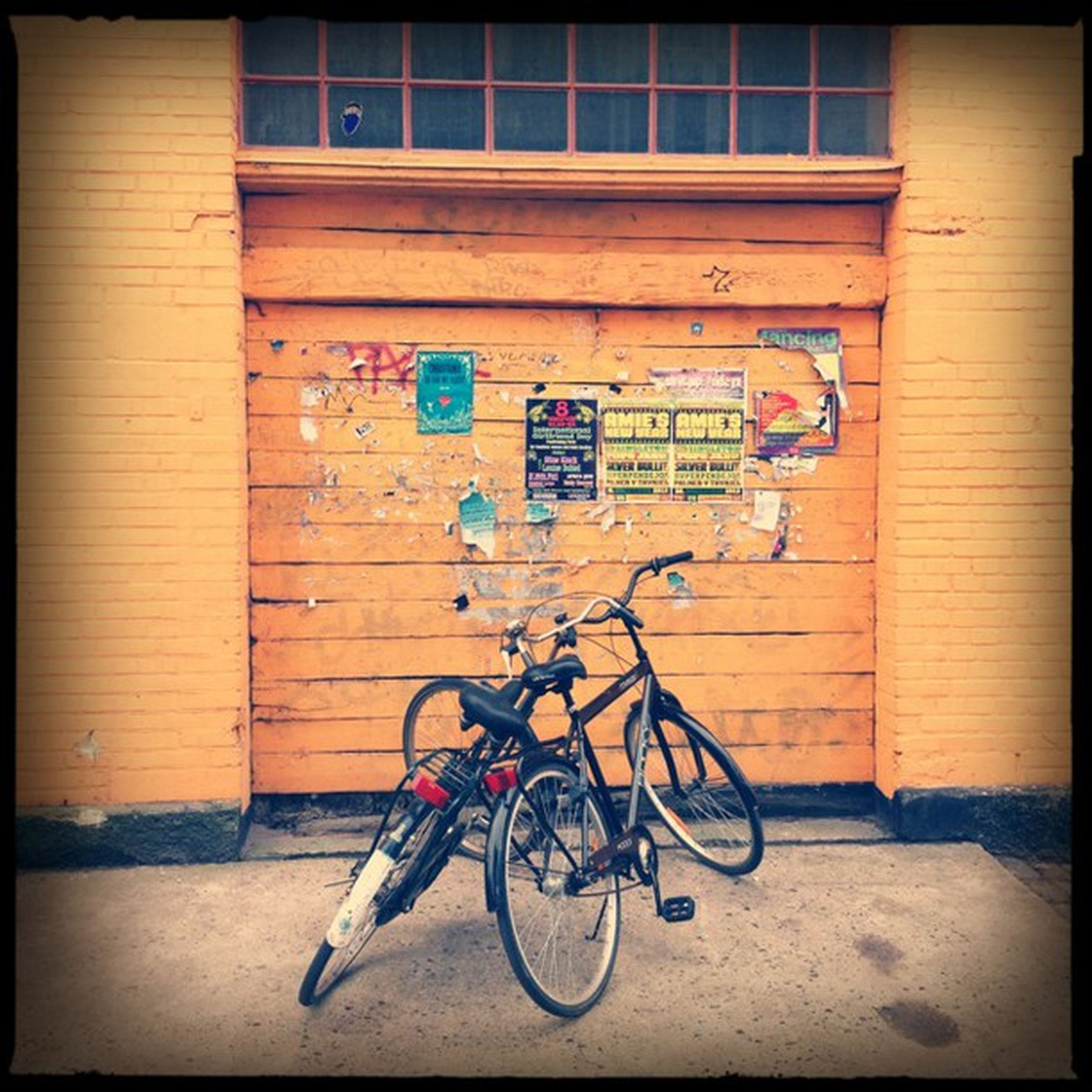bicycle, transportation, architecture, mode of transport, stationary, land vehicle, building exterior, parked, built structure, parking, text, wall - building feature, graffiti, western script, wall, communication, auto post production filter, sidewalk, street, day