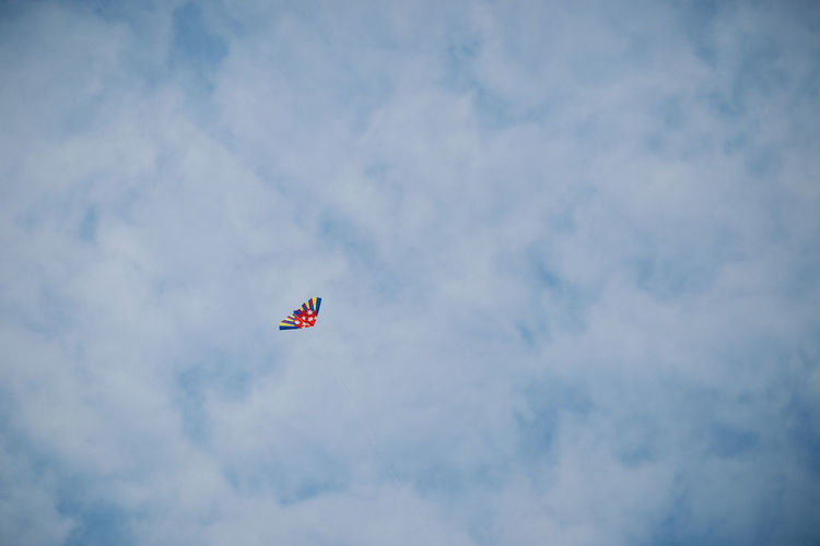 Low angle view of flag flying against sky