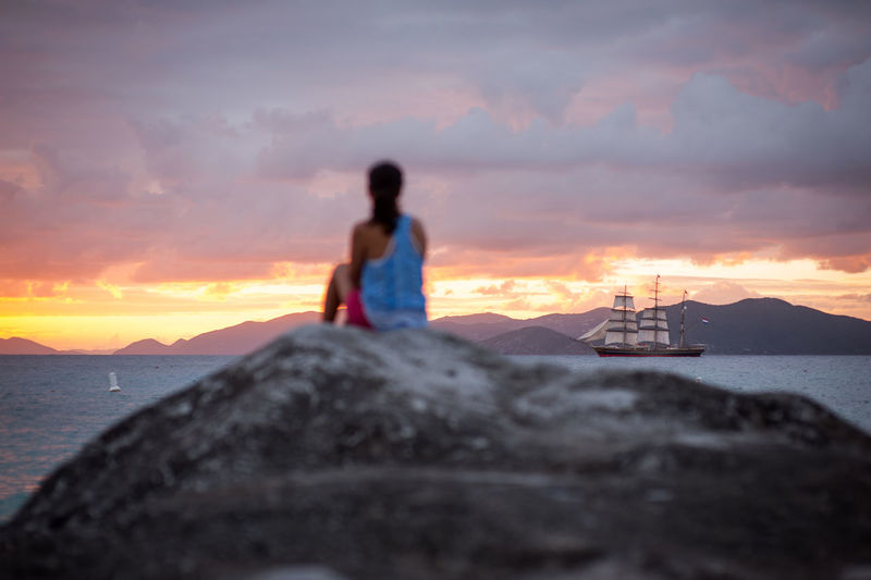 Man on rock at beach against sky during sunset