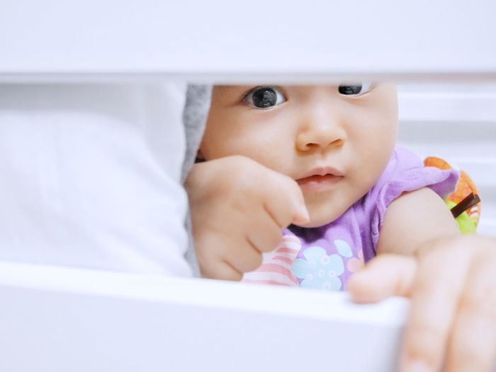 Close-up portrait of baby looking through crib