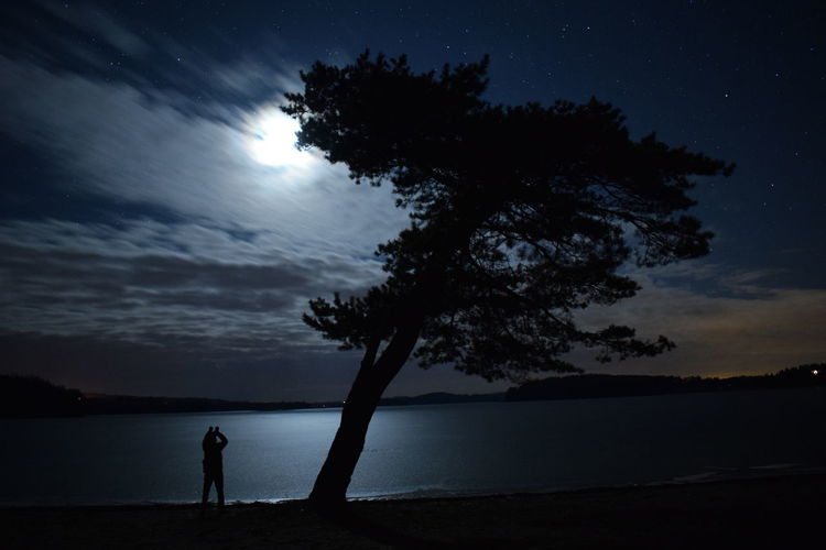 Astronomy Beach Beauty In Nature Cloud - Sky Dark Horizon Over Water Landscape Men Midnight Moon Light Moon Sky Clouds Cloud Nature Night One Man Only People Silhouette Single Tree Sky Star - Space The Frozen Lake Tree