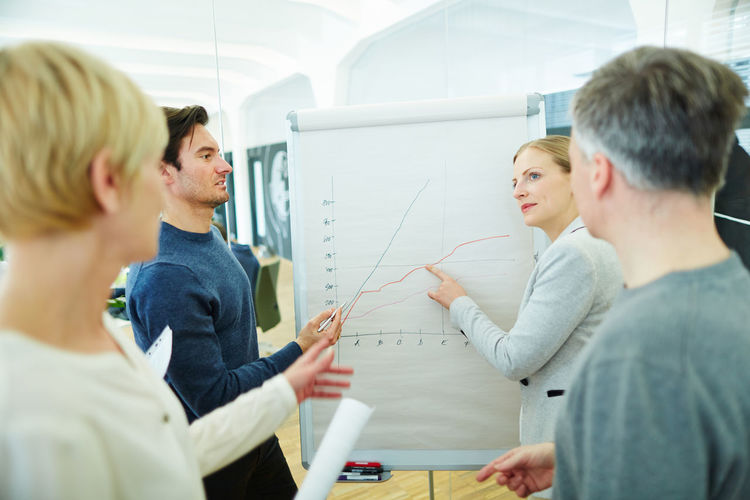 Businesswoman explaining graph to colleagues in office during meeting