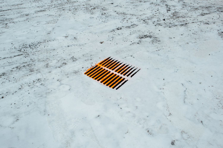 High Angle View Of Snow On Manhole