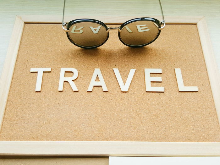 Travel board and sunglasses with reflection Sunglasses Travel Trip Holiday Vacation Material Wood Brown Board Communication Text Sunglasses Capital Letter Close-up Information Sign