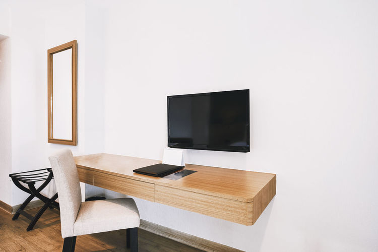 Modern hotel apartment room decoration with built-in furniture, utility desk, television, chair Decor Mirror Apartment Chair Copy Space Decoration Domestic Room Flooring Furniture Home Interior Home Showcase Interior Hotel Idea Indoors  Interior Design Living Room Mock Up Modern No People Seat Table Television Set Tv Wall - Building Feature Wood - Material