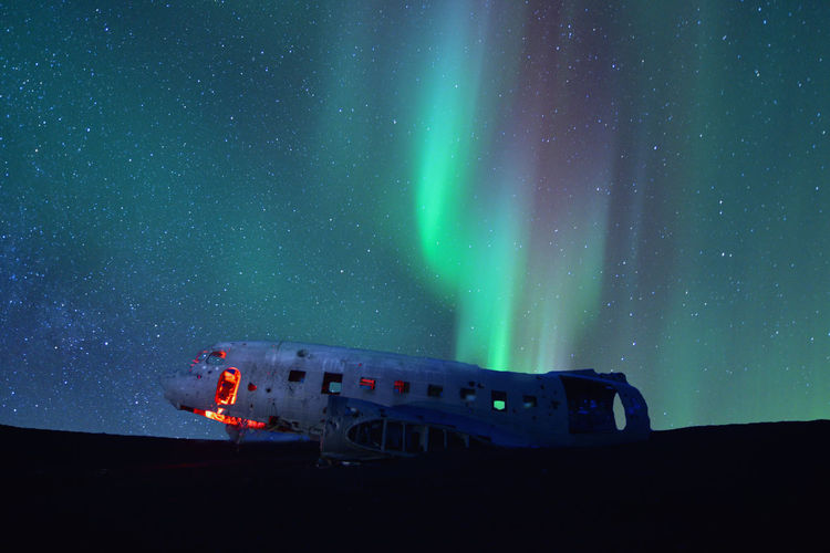 Northern lights over plane wreckage in iceland.old crashed military