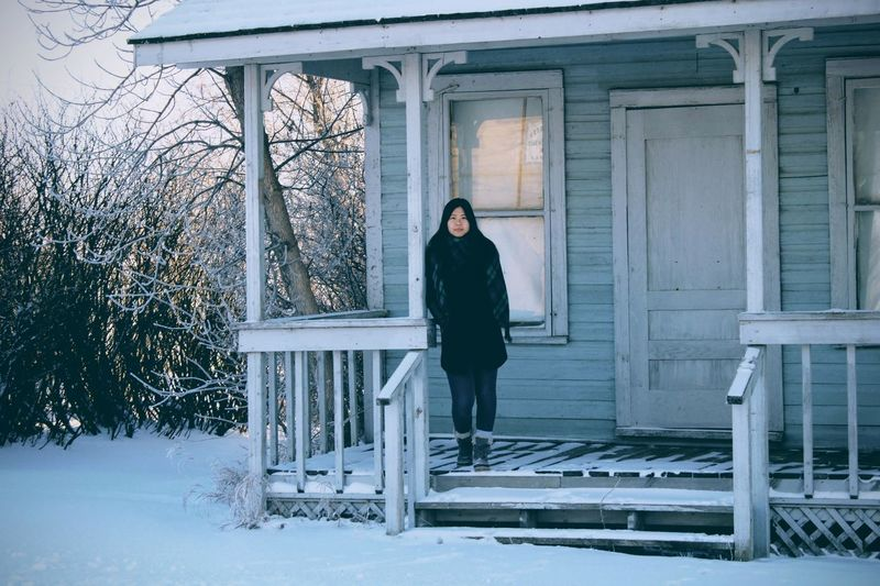 Portrait of woman standing at house entrance during winter