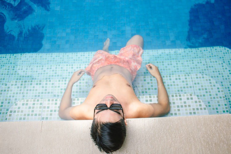 High angle view of shirtless man relaxing in swimming pool