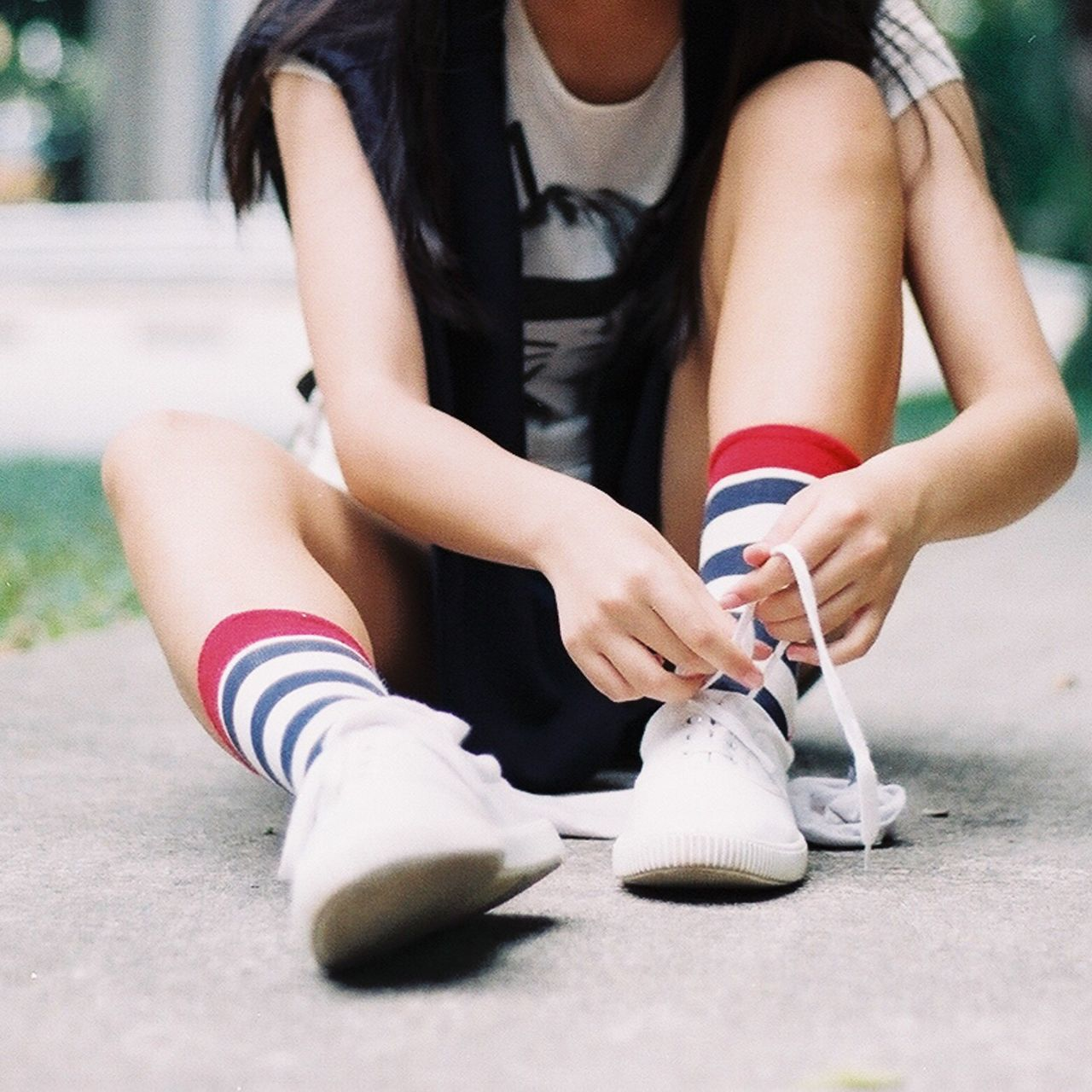 Low section of young woman tying shoelace while sitting on footpath