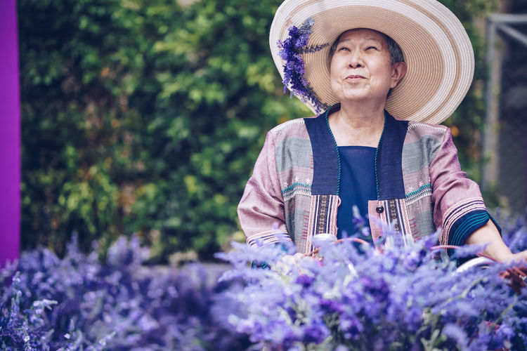 Low angle view of woman standing on purple flowering plants