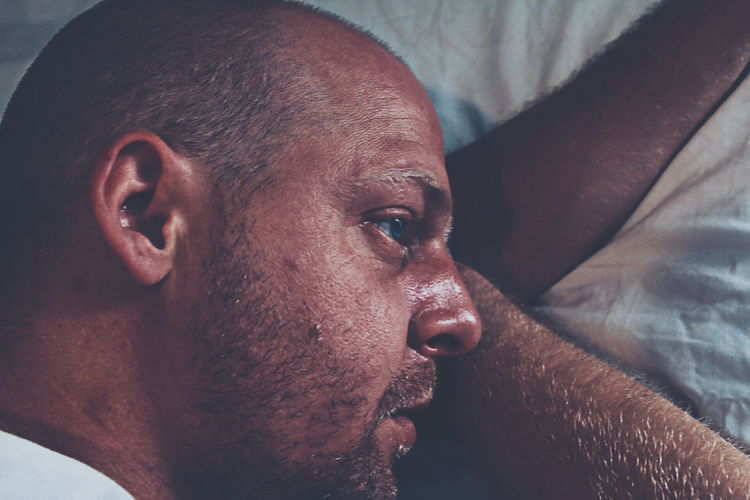 Directly above shot of thoughtful man lying on bed