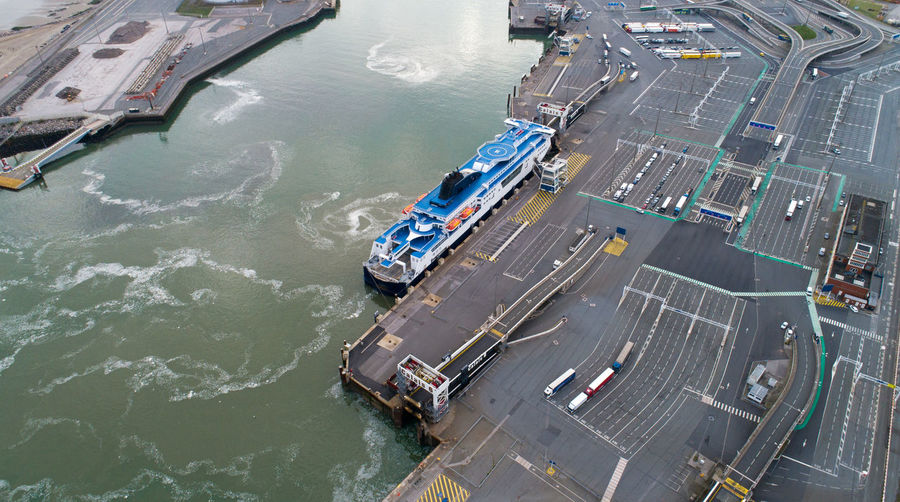 Aerial view of a ferry boat in Calais port, France Atlantic Ocean Channel City France Marina Pas De Calais Pier Aerial Photography Aerial View Blue Calais  Dock Freight Transportation French Harbor Industry Mode Of Transportation Nautical Vessel Parking Port Sea Ship Shipping  Trucks Water