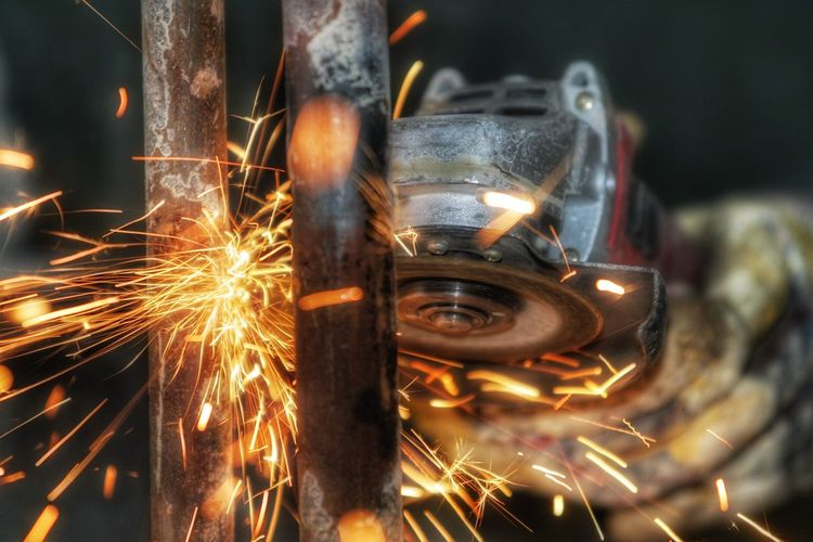 Close-up of person using angle grinder