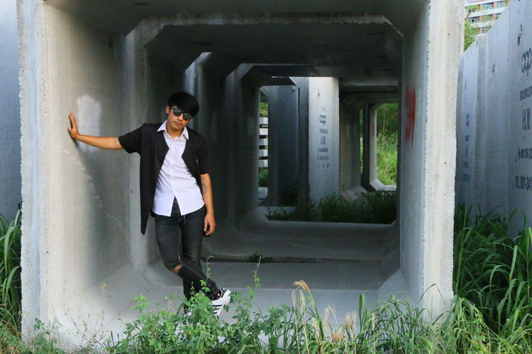 Portrait of young man standing in concrete structure
