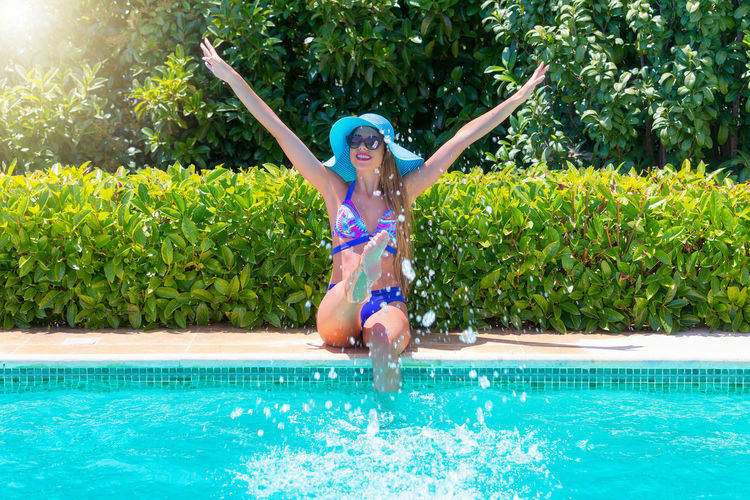 Full Length Of Happy Young Woman Splashing Water In Swimming Pool During Sunny Day