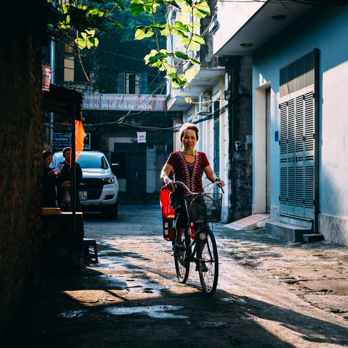morning Architecture Bicycle Building Exterior Built Structure City Day Full Length Land Vehicle Men Mode Of Transport Outdoors People Real People Transportation Tree Two People Young Adult