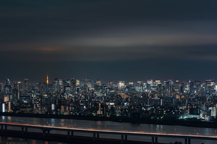 Illuminated cityscape by river against sky at night